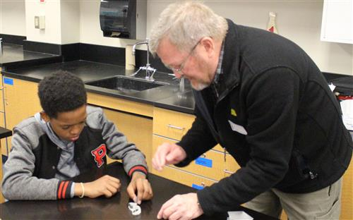 Student Walter Garrison and engineer Dale Josephson work with prisms.