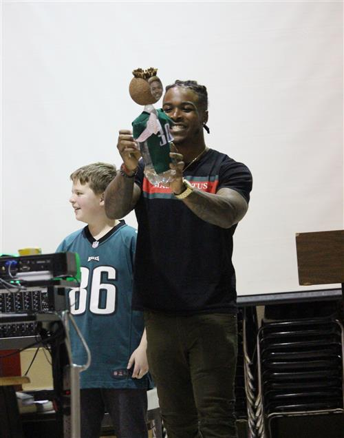 Corey Clement shows the students the bottle-head figure.