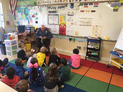 SRO Gio is pictured reading to students.